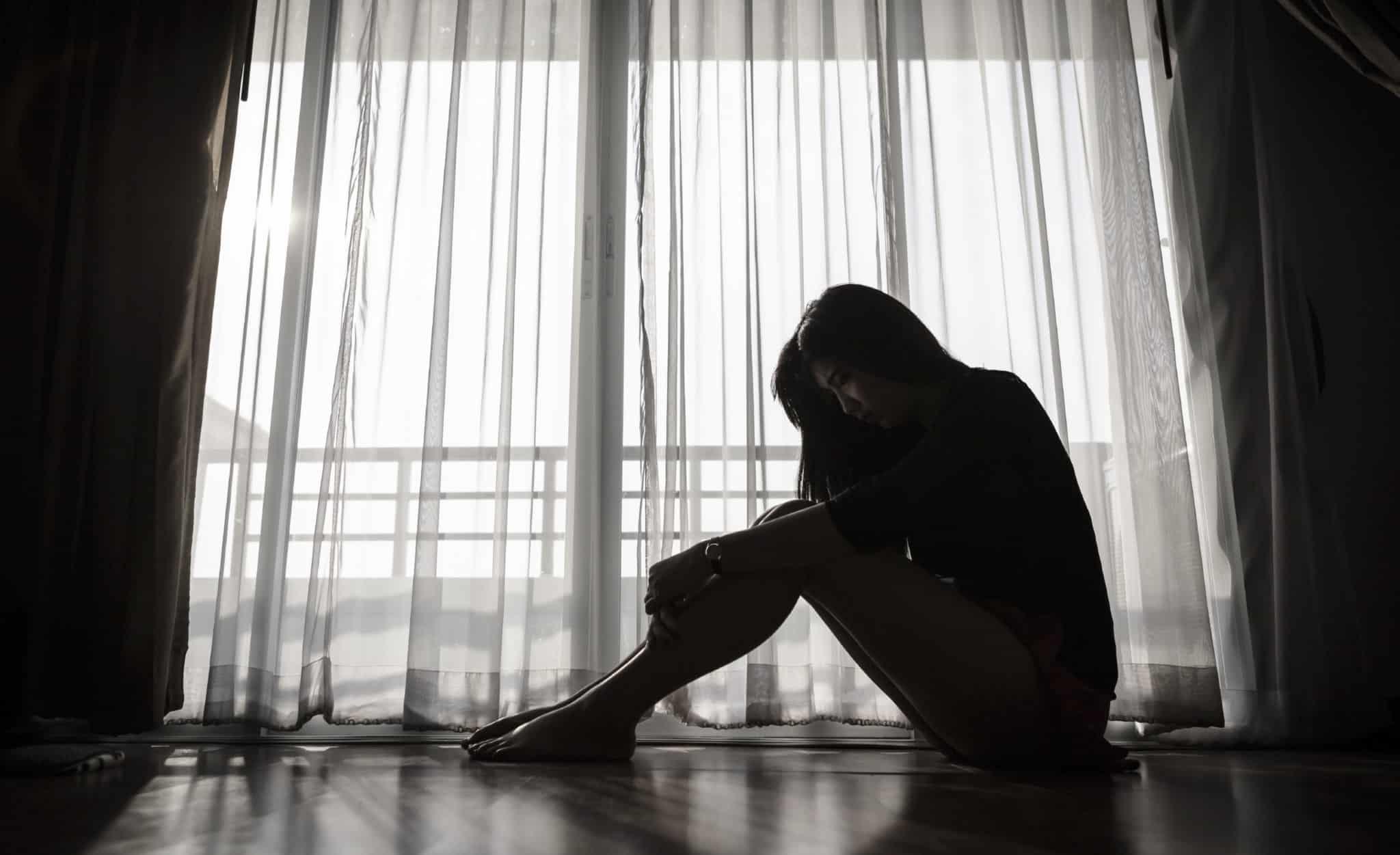 mulher com depressão sentada sozinha triste