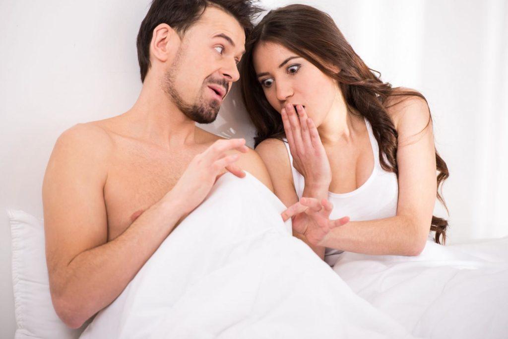 Erectill mulher olhando para o pênis do parceiro embaixo das cobertas surpresa