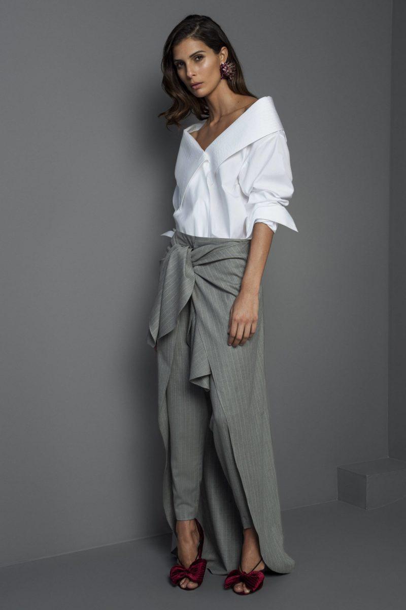 mulher com camisa de frio e uma calça cinza
