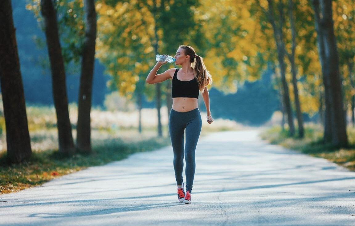 mulher caminhando e bebendo água