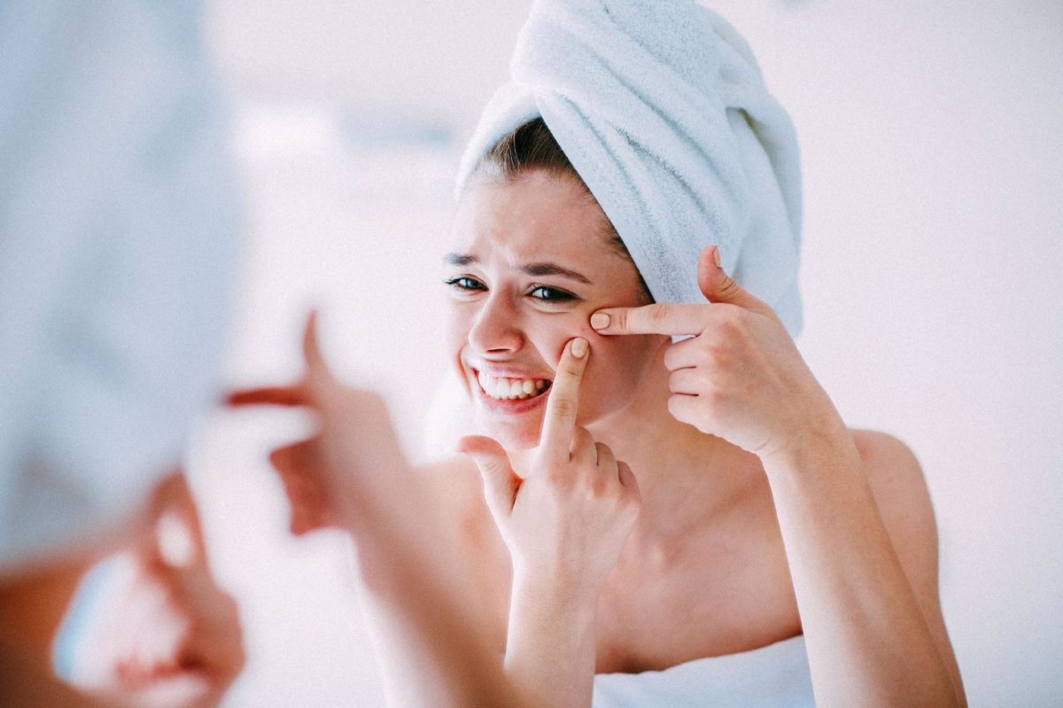 mulher se olhando no espelho tentando tirar a espinha
