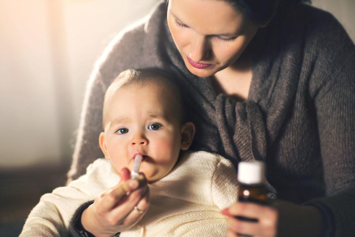 mulher dando complexo vitaminico infantil para um bebe