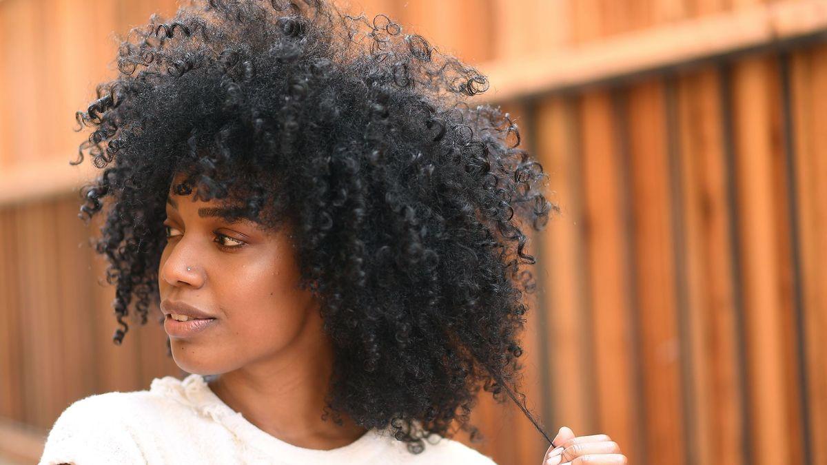 mulher negra com cabelo de permanente afro