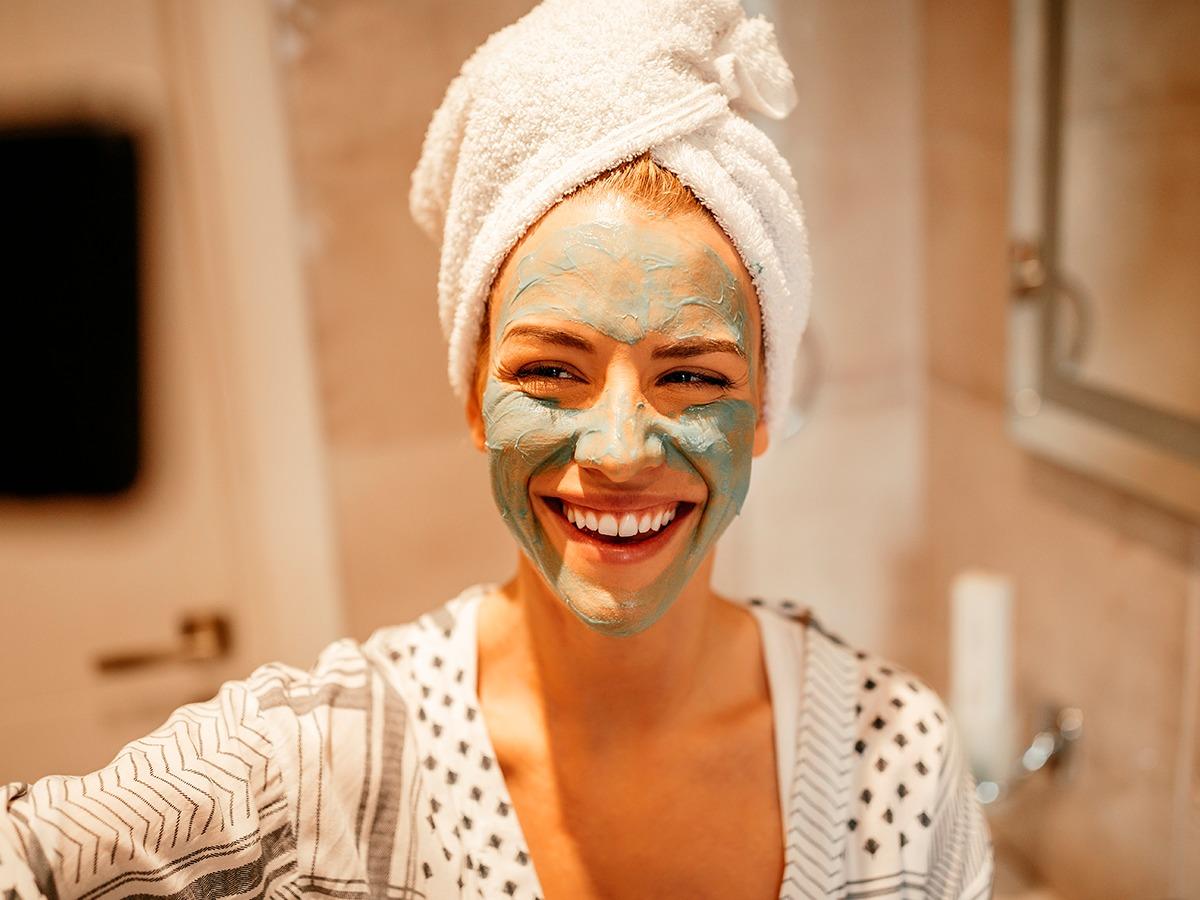 mulher com o rosto coberto de argila verde