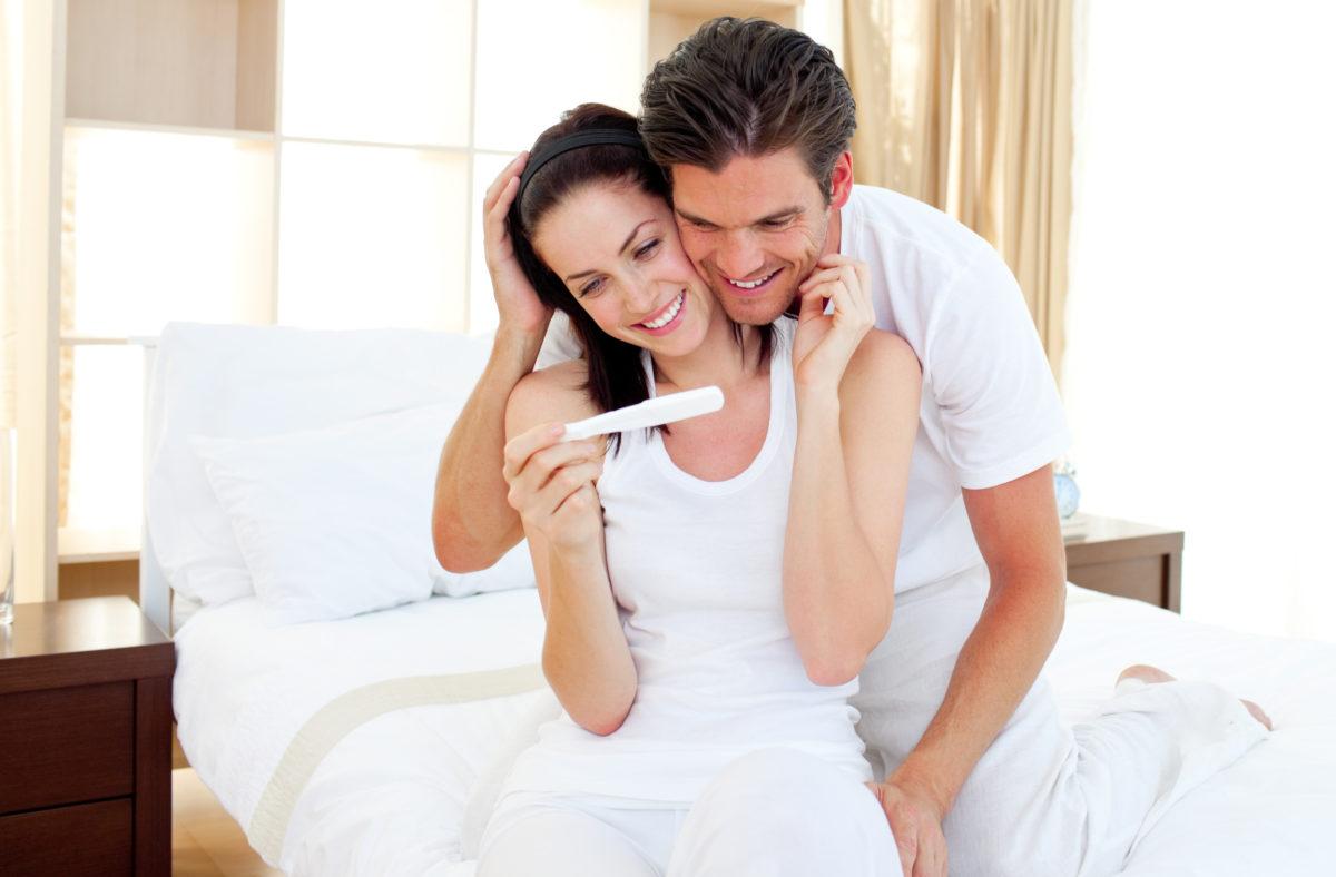 casal feliz olhando o teste de gravidez positivo graças ao fertil caps