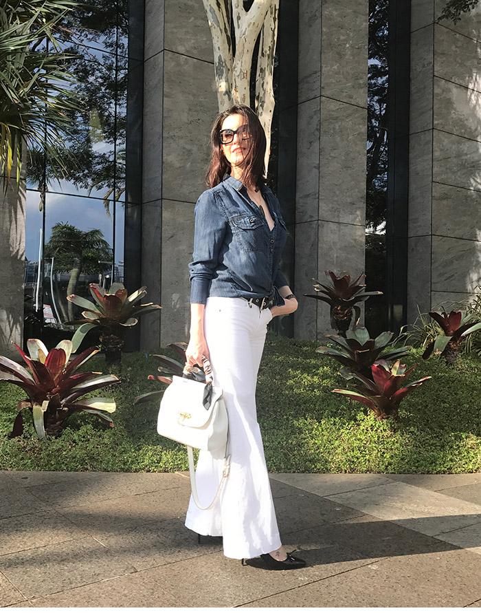 mulher com calça flare branca e camisa jeans