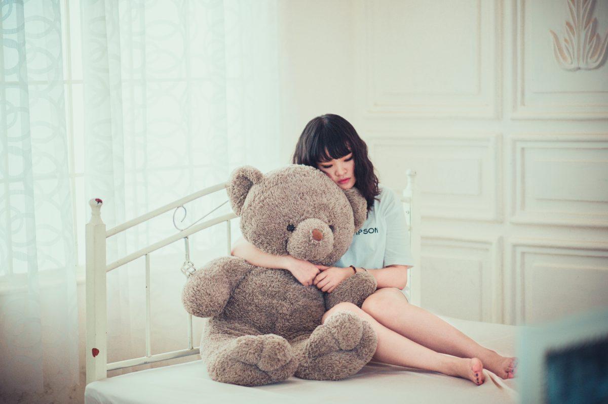 foto de menina segurando um urso triste